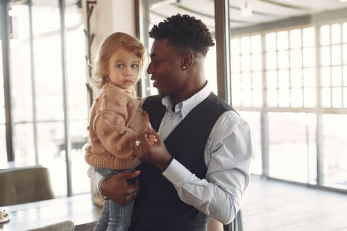 Positive ethnic man holding little girl on hands while standing in cafe