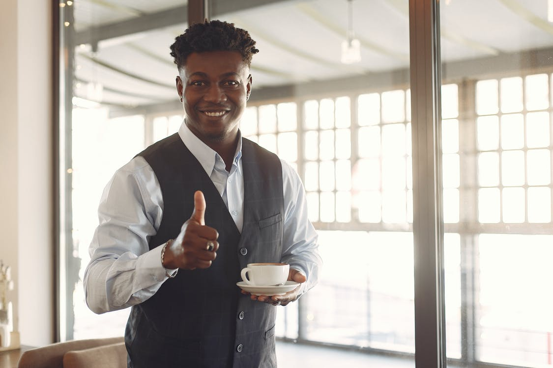 Smiling young ethnic businessman standing in cafe with cup of coffee and showing thumb up