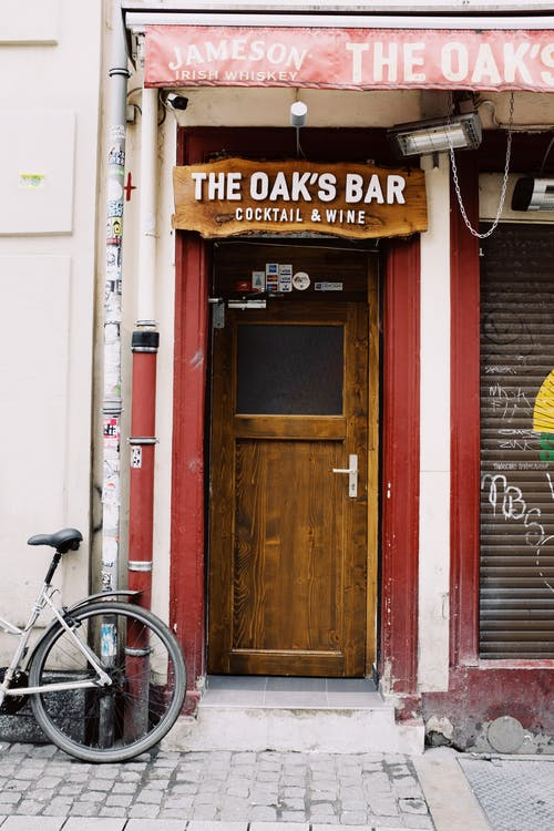 Door of closed bar with signboard and bicycle parked near entrance