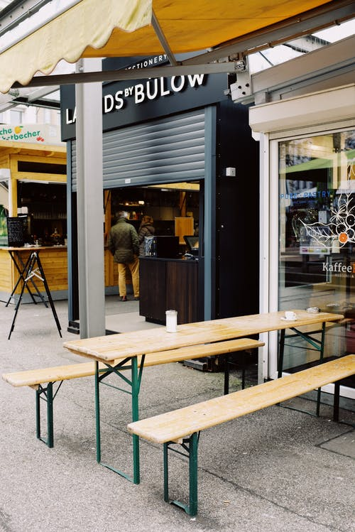 Terrace of modern street cafe with wooden furniture on street