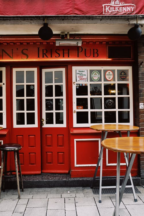 Exterior of modern pub with red signboard and red door with stylish wooden tables near entrance on street