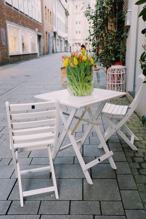 White wooden chairs and table with colorful tulips in vase placed near cafe on street