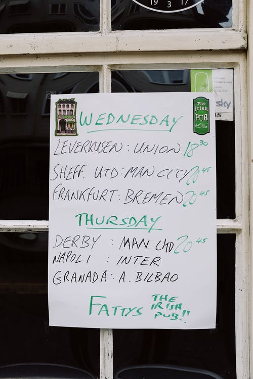 White blackboard with handwritten timetable hanging on glass door on entrance of pub
