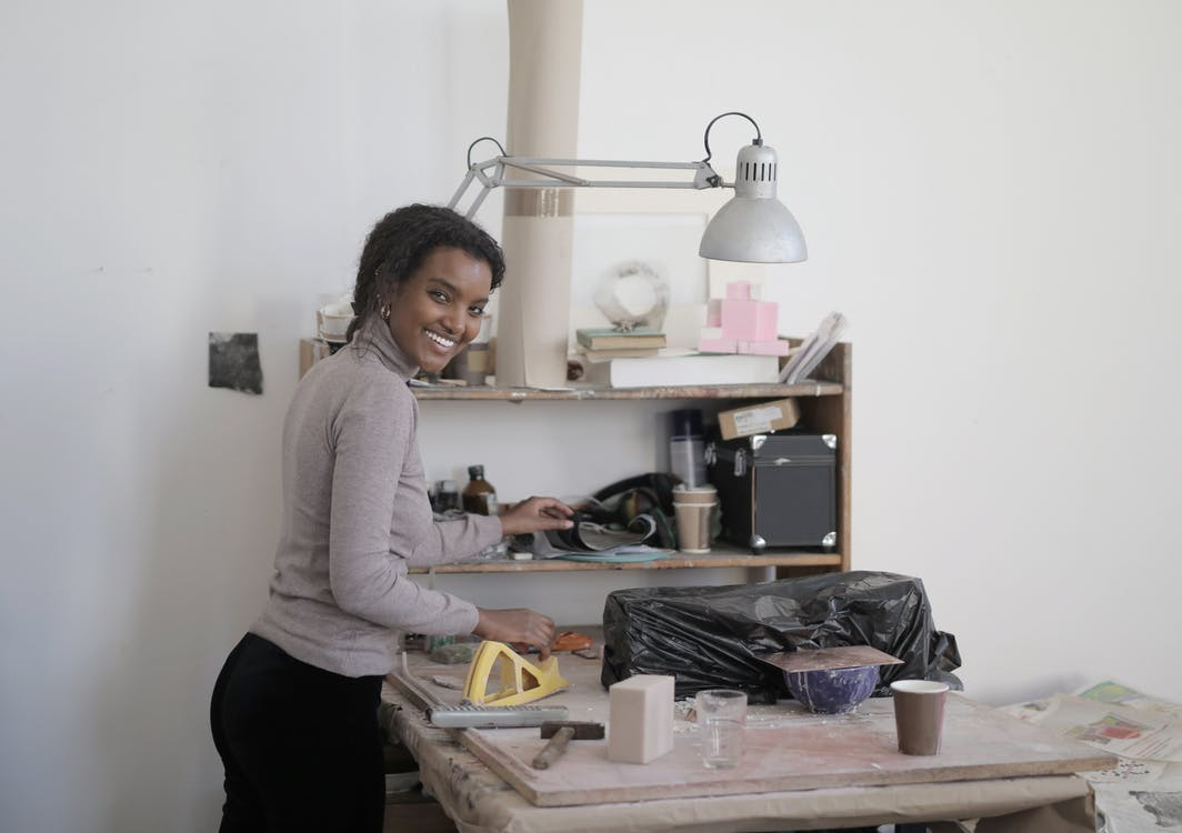 Side view of cheerful young black woman standing near workbench in light modern workshop and looking at camera