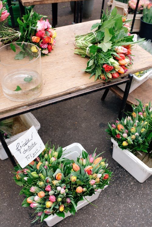 Buckets of fresh flowers on table and in boxes on street market