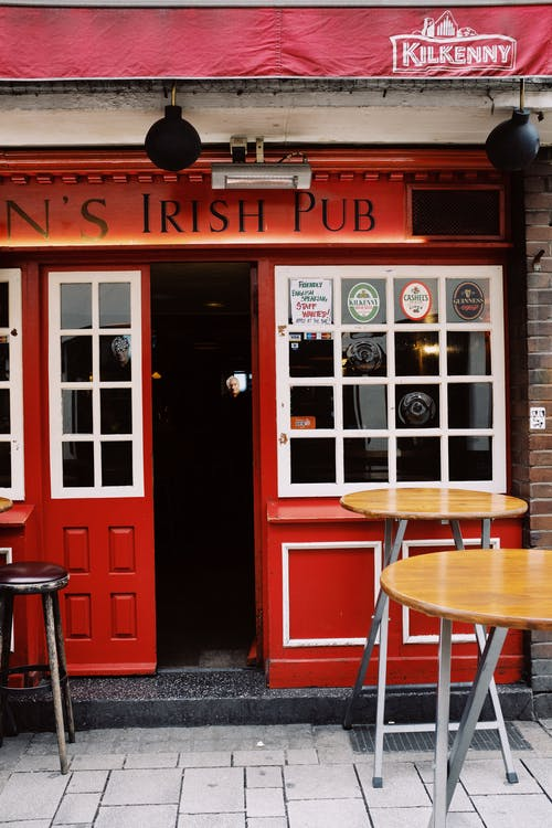 Entrance of modern pub with bright signboard and wooden tables