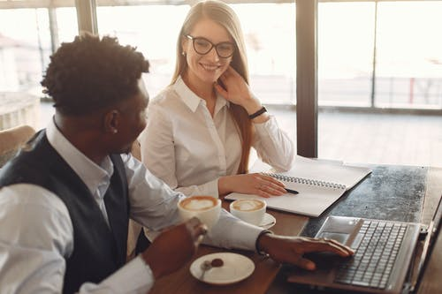 Side view of positive young multiethnic coworkers in formal clothes sitting at wooden table and drinking coffee while working together in modern workspace