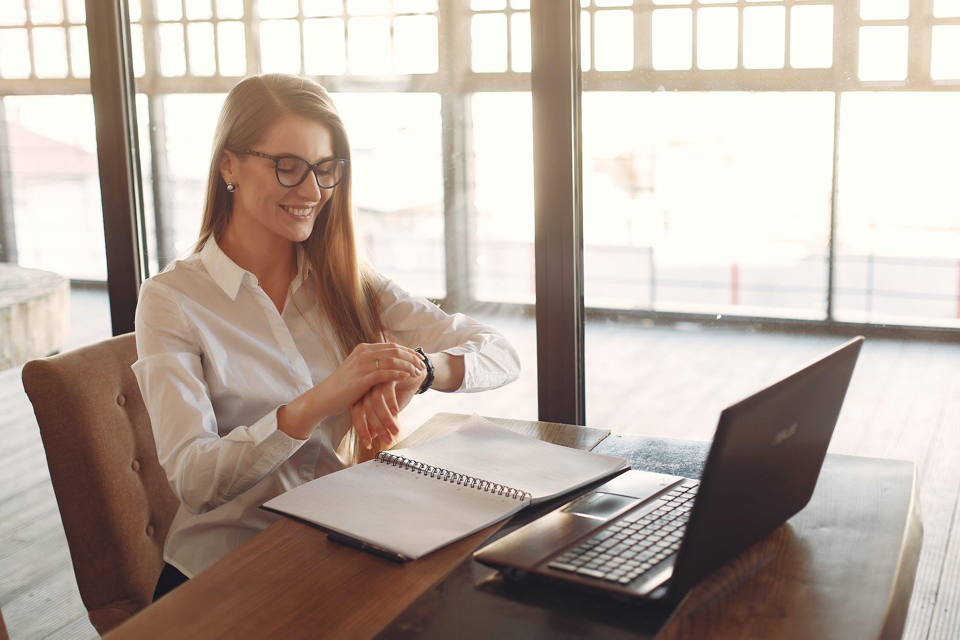 10 percent life blog | mujer viendo su reloj frente a su laptop