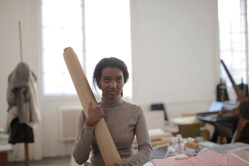 Young female ethnic worker in casual clothes standing near workbench with paper roll and looking at camera in modern workshop
