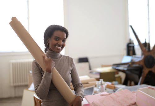Positive young ethnic craftswoman holding paper roll in light studio