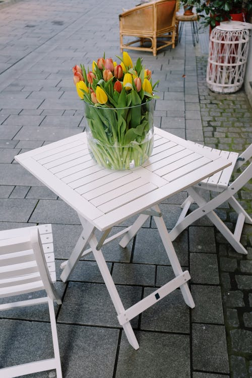 White wooden table with flowers in vase and chairs outside cafe