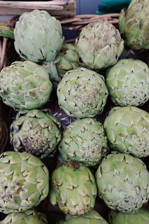 Set of fresh green artichokes placed in wooden basket on market
