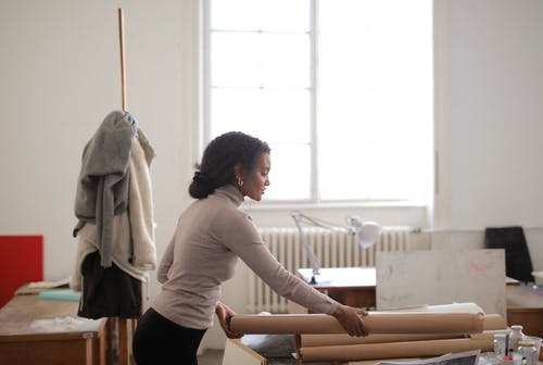 Side view of young female in casual clothes prepares kraft paper for drawing while working in creative studio at daytime
