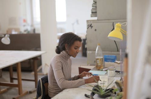Creative female designer drawing sketch on paper in light studio