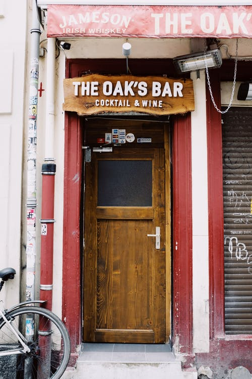 Retro bar with closed street blinds and wooden door at daytime