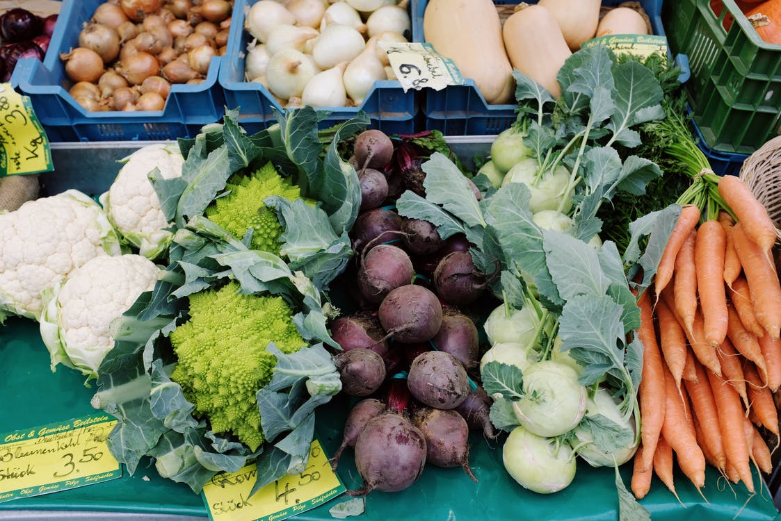 Variety Of Vegetables on Blue Plastic Crates And Table