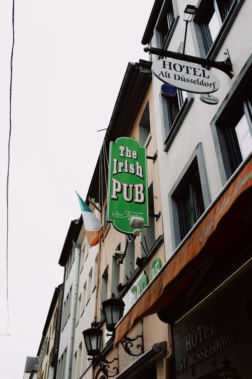 Low angle of old fashioned buildings of hotel and Irish pub decorated with lanterns and flag of Ireland in city