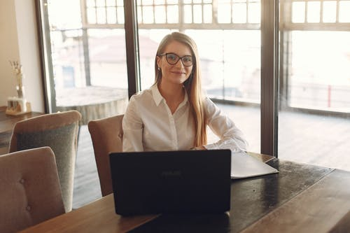 Woman in White Polo Shirt Sitting  In Front Of A Black Laptop