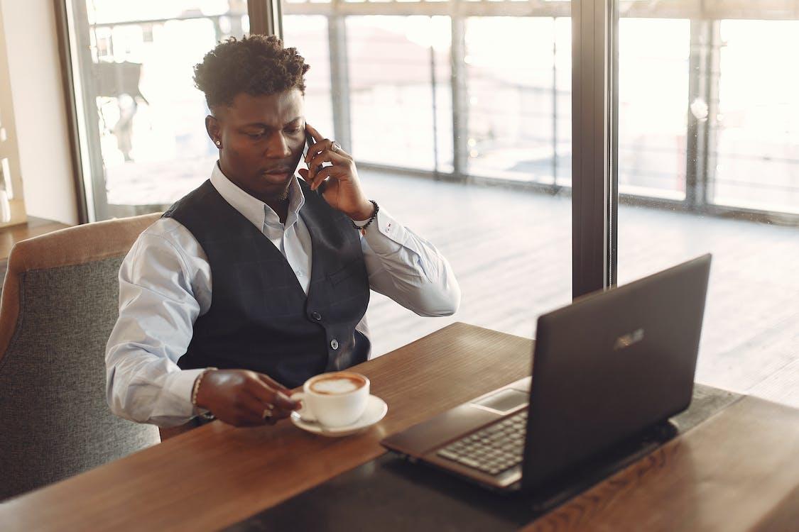 Man in White Shirt Working While Having Coffee