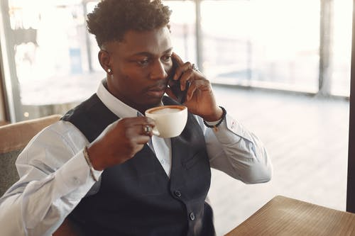 Man Drinking Coffee While Having Conversation Over The Phone
