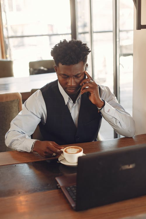 Serious African American businessman talking on smartphone during coffee break using laptop in cafe