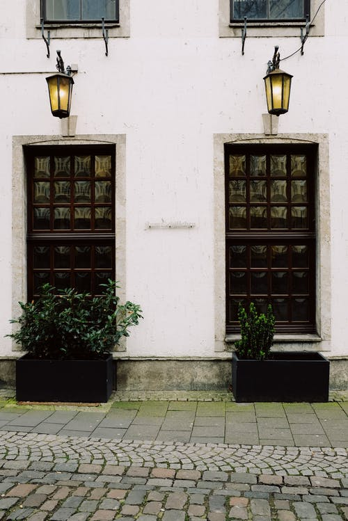 Exterior of aged stone house with potted plants and lighted lanterns above ornamental doorways on cobblestone street