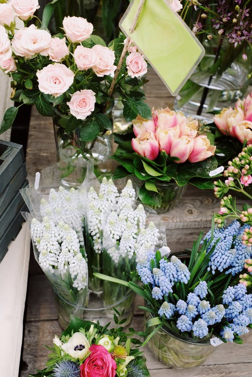 From above different types of fresh flowers in vases with water placed on wooden steps for retail in flower store