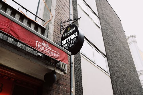 Signboard of beer pub near modern brick building in tourist city