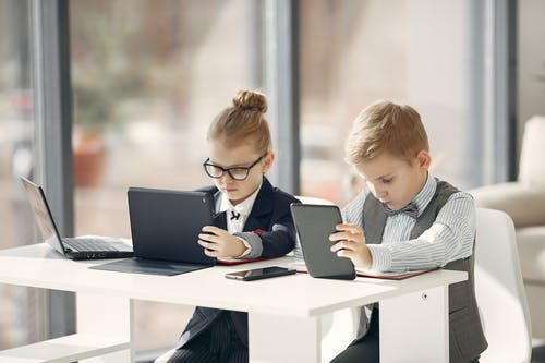 Focused cute children using tablets near laptop and smartphone in modern office