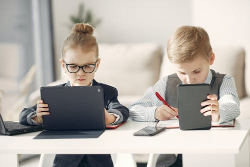 Concentrated little kids taking notes in organizer and working on tablets in workspace