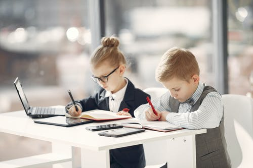 Focused kids colleagues writing notes in daily planners in modern office
