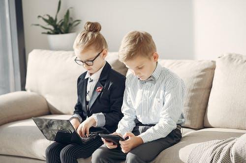 Adorable preschool executives using gadgets on sofa in creative office