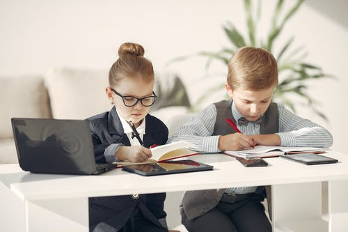 Focused preschool managers taking notes in organizers during working day