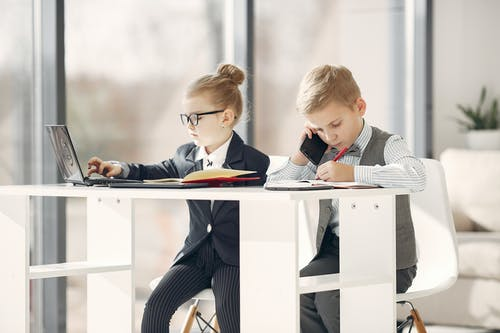 Little preschool manager in uniform talking on phone and taking notes in planner while girl colleague in formal wear and glasses using netbook in modern studio