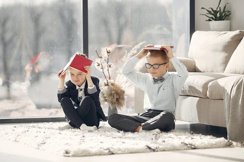 Full body happy little students in uniform and eyeglasses sitting on floor near sofa and window putting books on head while staying in modern room