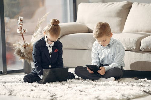 Full body of concentrated preschool coworkers using gadgets during work at home
