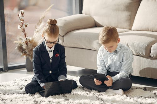 Focused little freelancers browsing laptop and tablet in modern apartment