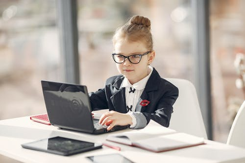 Confident executive girl browsing netbook in modern workspace