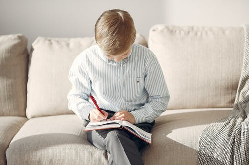 Boy in Black and White Stripped Shirt Sitting on Couch Writing on Book