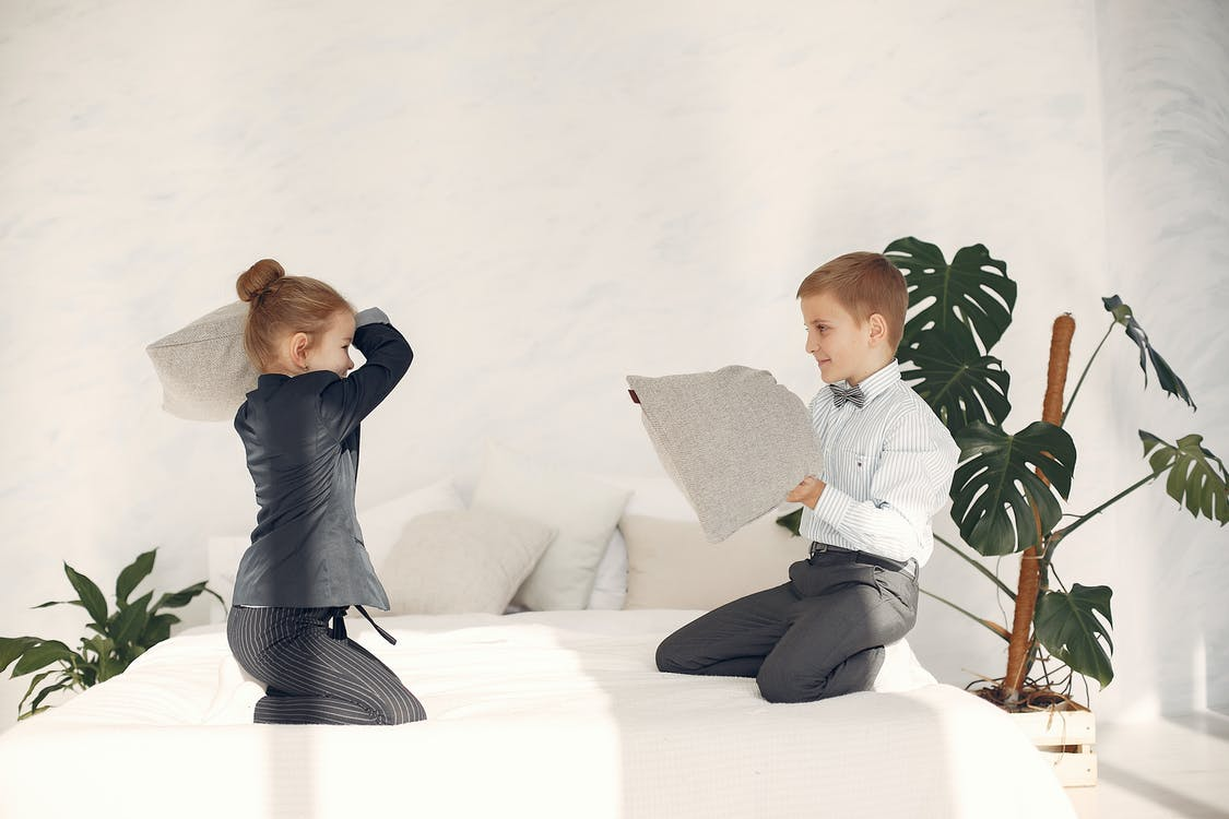 Happy little business kids having fun together during game with pillows