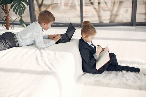 Side view of attentive cute boy using laptop while lying in bed together with adorable serious girl sitting on fluff carpet near bed and taking notes in diary in modern apartment with white interior
