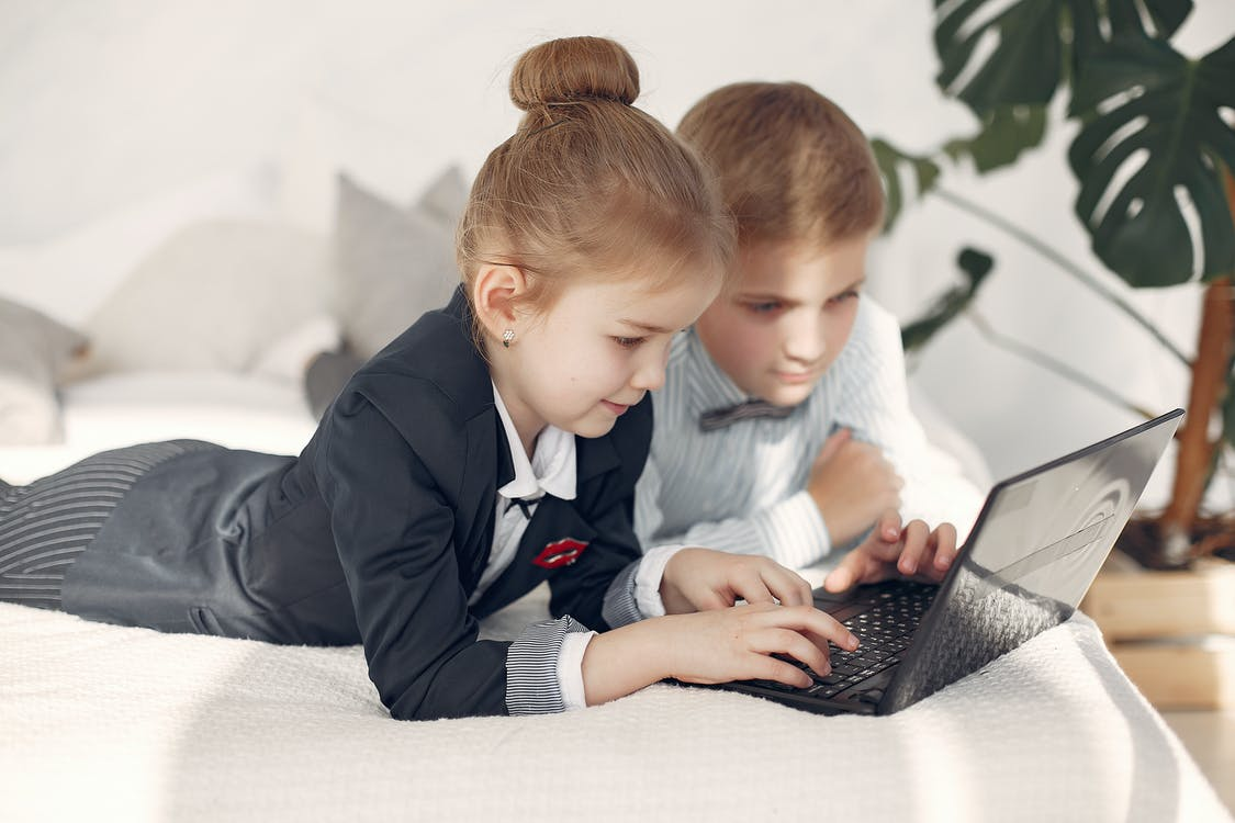 Smart little business children in formal outfits working with laptop remotely in team