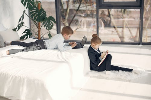 Side view of smart cute boy using laptop while lying in bed together with adorable serious girl sitting on fluff carpet near bed and taking notes in planner in modern room with glass wall