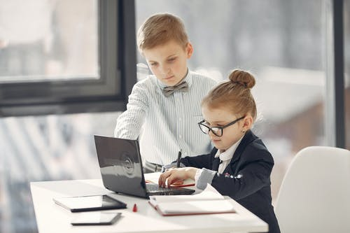 Professional little entrepreneurs with laptop in modern office