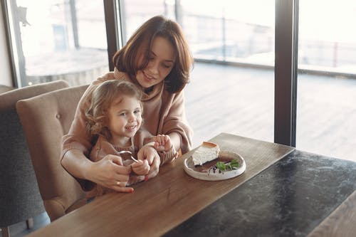Mother and daughter having dessert in cozy cafe