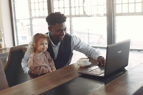 Happy young African American man looking after little girl in cafeteria using laptop