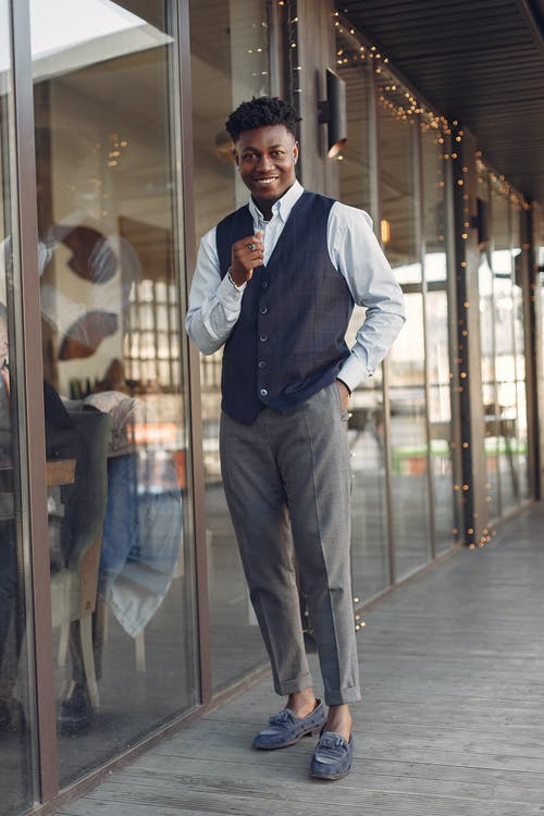 Cheerful stylish black man in formal outfit and trendy loafers outside modern cafe