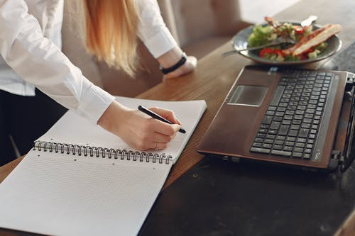 Young businesswoman working remotely in cafe during lunch time