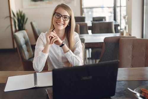 Cheerful young businesswoman in eyeglasses during remote work in cafeteria