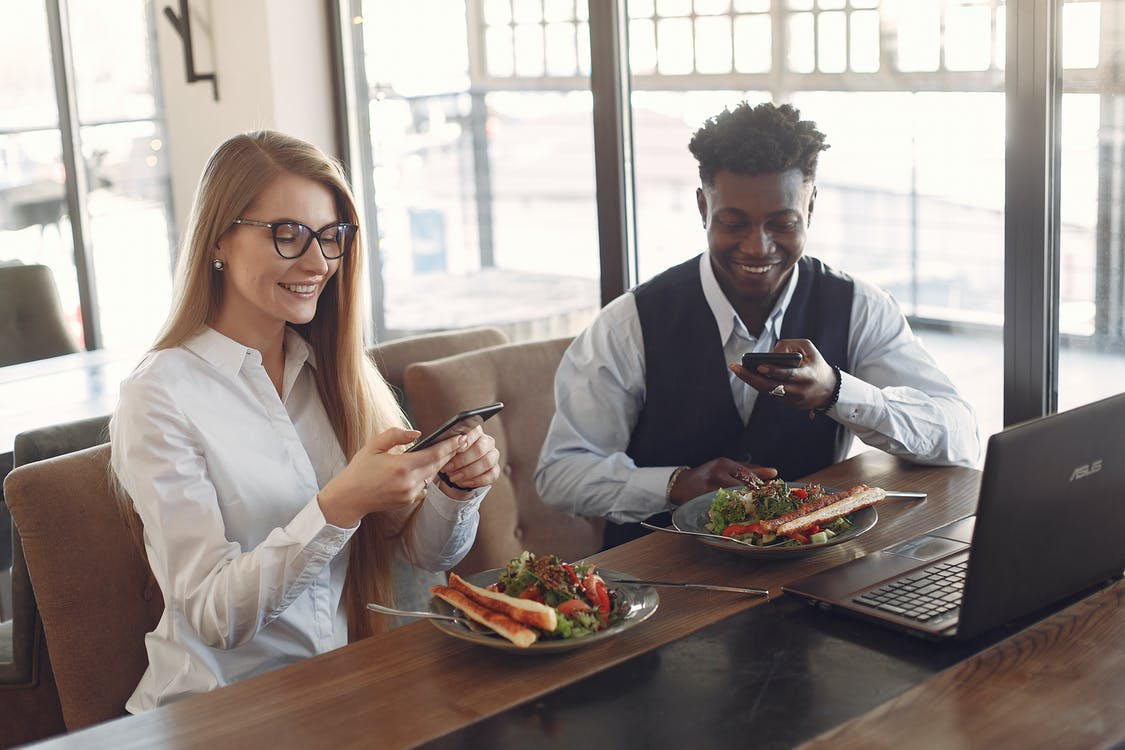 Cheerful diverse colleagues using phones during business lunch in cafe